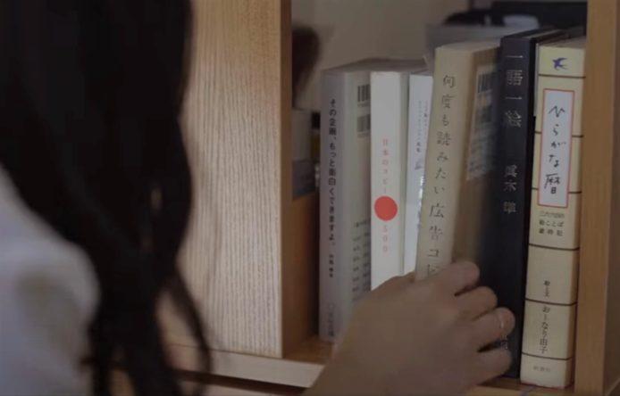 『何度も読みたい広告コピー』という本を手に取る女性の後ろ姿。他にも本が5冊ほど並んでいる。