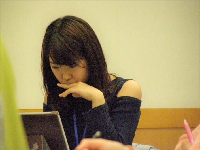 パソコンの前で手を口に当てながら考え込む長髪の若い女性。他にも数名が勉強している模様。